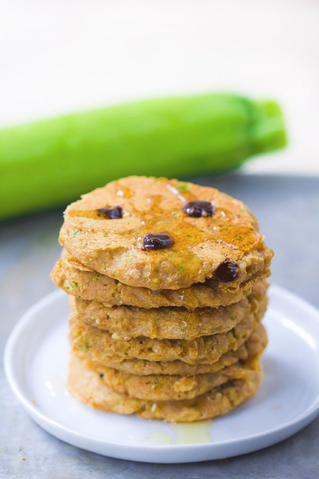 A giant stack of extra fluffy zucchini pancakes, stuffed with melty gooey chocolate chips and covered in hot maple syrup - These disappear so quickly whenever I make them: http://chocolatecoveredkatie.com/2015/08/10/zucchini-pancakes-healthy-vegan/